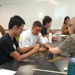 Students build marshmallow towers. Discussion focuses on experimentation, failure, and success.